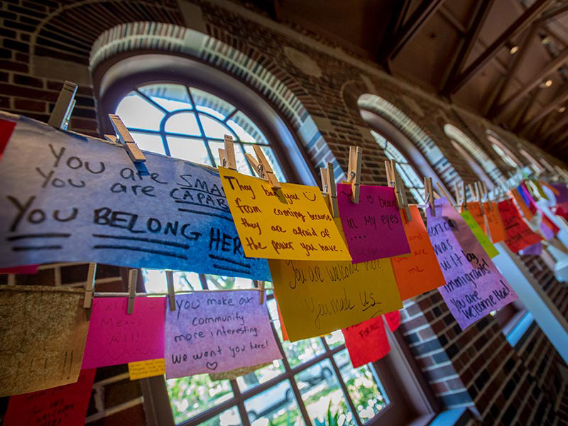 "In the foreground, a string is strung across a room with clothes pins holding handwritten quotes on colorful cards. The cards say ,""You are smart, you are capable, you belong here,"" and ""They ban you from coming because they are afraid of the power you ha"