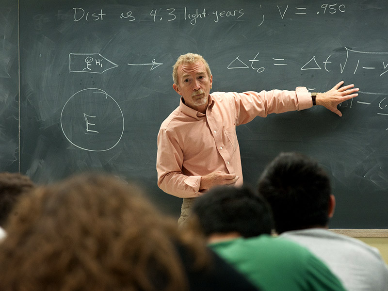 Instructor standing front of chalk board and gestures to symbols written on chalk board.