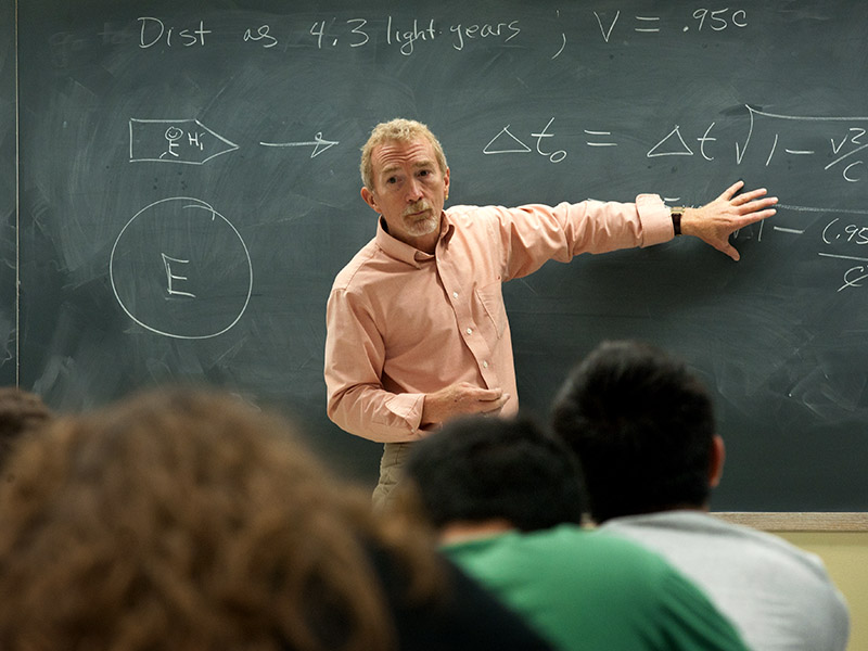 A professor stands in front of a chalk board with writing on it.