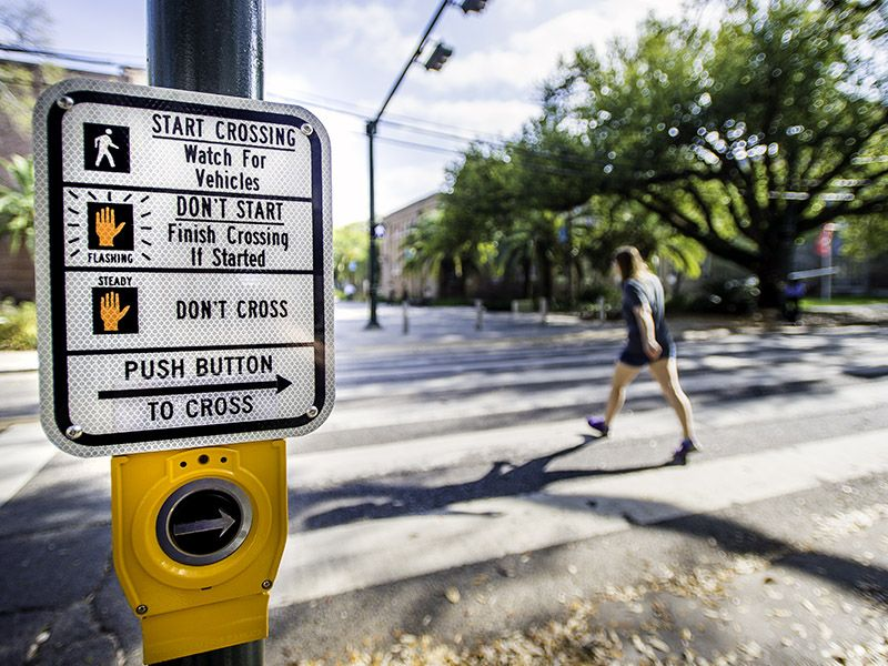 Instructions for button that triggers crosswalk lights with blurred student crossing street in background.