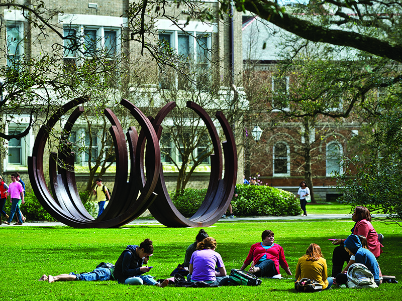 Students sitting in the grass near a round sculpture.
