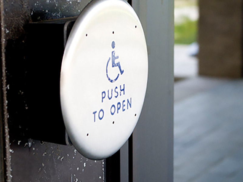 A close up of a hand press handicap assistant button to open the doors.