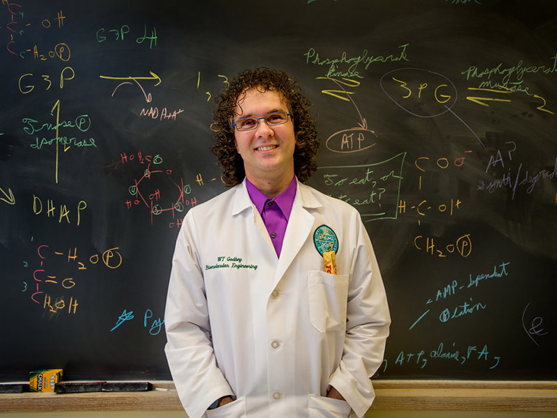 A faculty member in a lab coat stands in front of a chalkboard covered in colorful math equations.