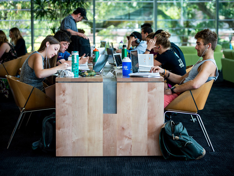 A group of students sits around a table in the LBC studying.